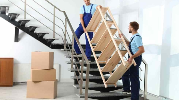 Professional workers carrying wooden rack on stairs in office. Moving service